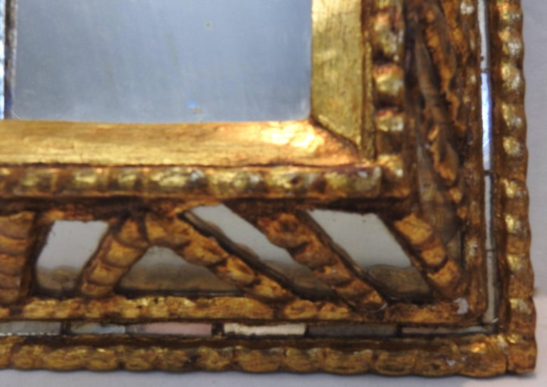 Featured is a unique mirror with panes of silvered glass surrounded by distressed gilt over gesso. The different dimensions will catch your eye as you walk by. A metal loop is mounted on the back for hanging.