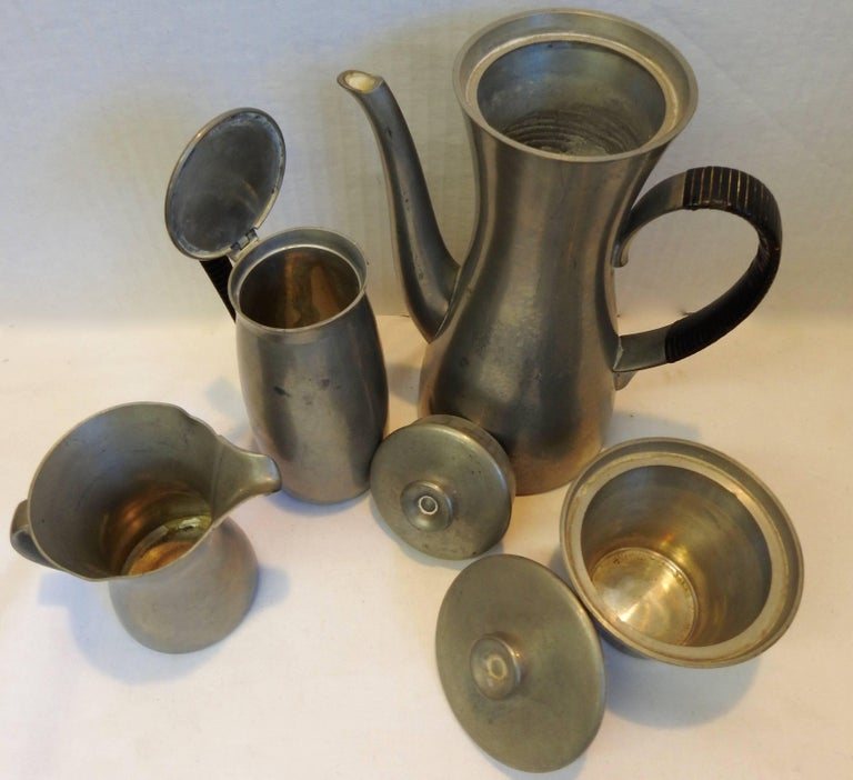 Royal Holland manufactured this midcentury tea or coffee set. It consists of a coffee or tea pot along with a sugar and creamer and a container for your waste of tea leaves or grounds. The handles of the two larger containers are wrapped in a black