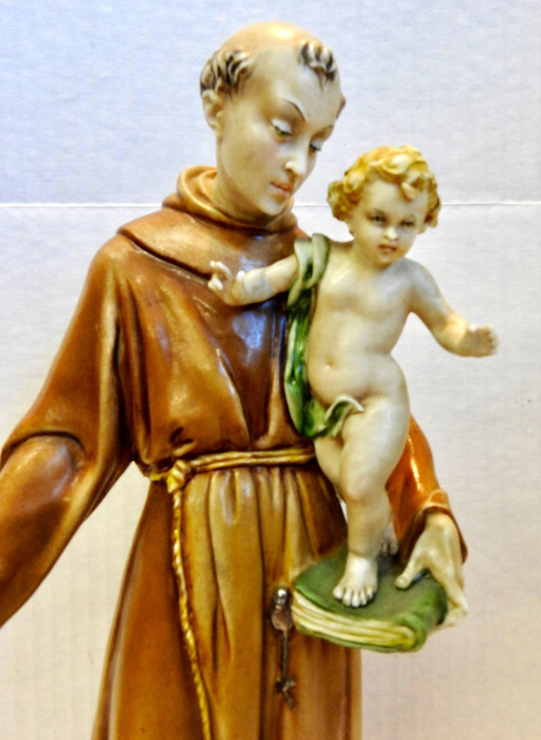 Saint Anthony is holding a cherubic child on his book and is looking at him lovingly. The porcelain has been glazed in soft colors. The figurine is marked in the back and on the bottom.