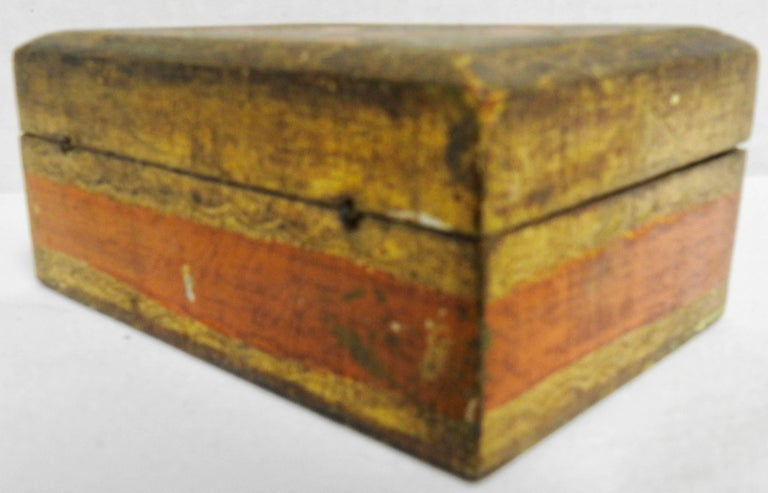 Featured is a small Florentine box from Italy, made during the mid-20th century. It is decorated with gilt along with detailed tangerine orange and a touch of emerald green. The inside is finished in a soft yellow. Tiny wires serve as the hinges.