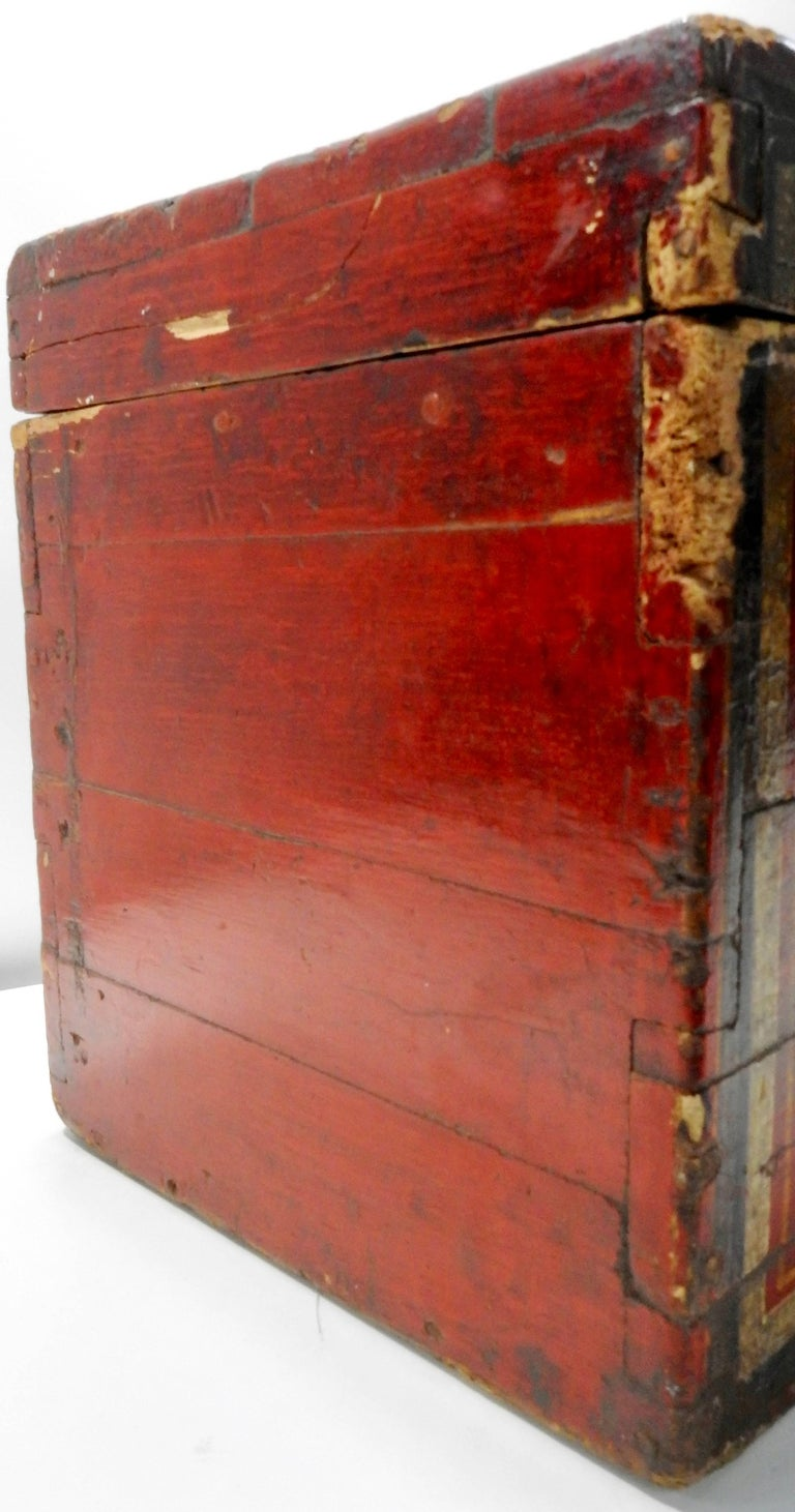 Vibrant red sings on this stunning wooden box from the 19th century. It is highlighted with flowers in black and gold along with the edges trimmed in these colors. There is a metal clasp to secure the lid.