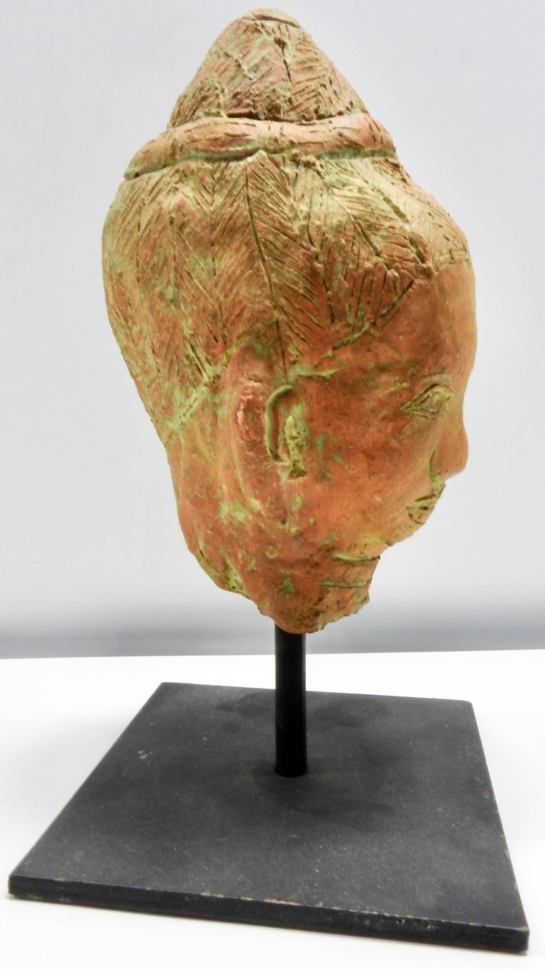 Details speak volumes on this terracotta sculpture of a head that is perched on an iron stand. The natural terracotta color is enhanced with soft green highlights. The head measures 8