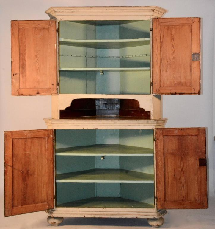 This piece is in a beautiful cream color with yellow doors. It boasts a pretty turquoise color on the inside with multiple shelves. It has a cubby hole between the top and bottom to display your treasures. The cabinet sits on turned bun feet. The
