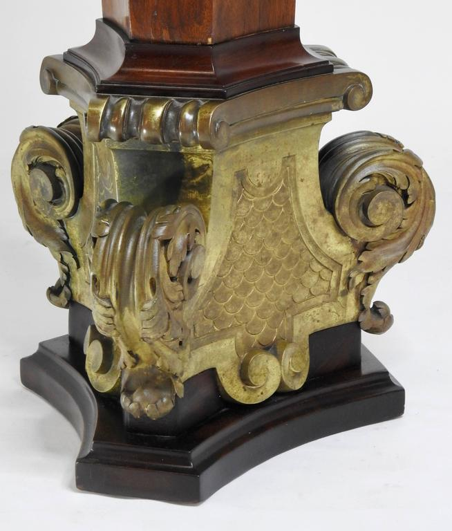 This beautiful piece starts at the bottom with a bronze base that features unique foliate and scrolling detail. As the body rises in the rich mahogany placed halfway on three sides is a bronze medallion that is circular and detailed with carving. It