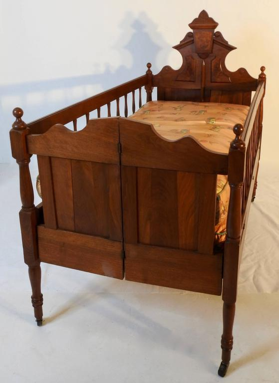 Burled walnut and Classic walnut grace this Victorian baby bed from the 19th century. Includes mattress and springs which is covered in a plastic vinyl type material with stitched seams. The bed sits on four casters rising on a turned wood leg.