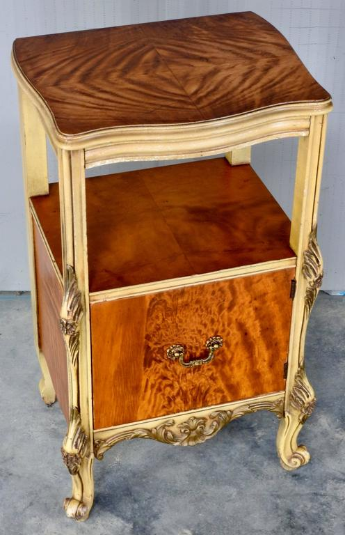 Elegant satinwood makes up a nightstand with ornate hand painted gold trim. Door opens with a cast bronze pull for storage. Two areas are available to display your treasures. The maker's tag is on the inside of the door. It was made by the J. B. Van