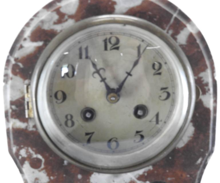 Lovely brown and white marble make up this matching set consisting of a clock and a pair of pedestals. The clear glass of the clock is enhanced with an etched floral design. The domed glass covers the metal clock face. The bronze hardware finishes
