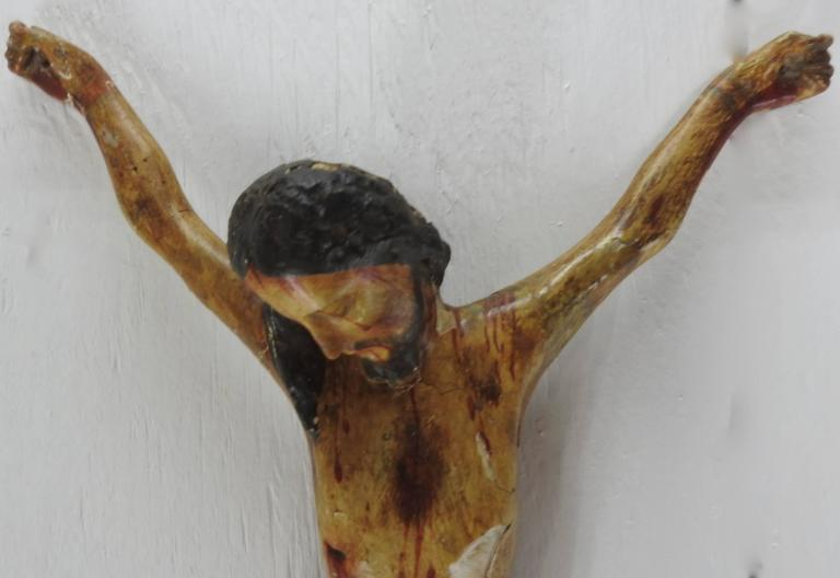 This is a rustic polychromed crucifix from Italy. Jesus is sadly hanging his head to the side. The soft colors add to the beauty of this piece. There is a wire inserted in the back for hanging on the wall.