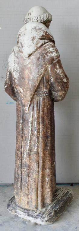 A cast stone garden statue of St. Francis of Assisi. The statue has been outside and has developed a weathered patina which adds to his character. The applied colors have faded over the years. He is holding a bird in his hands.