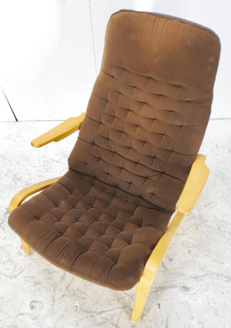 "We are featuring a Danish Modern lounge chair by Dux. This chair features a button tufted, brown upholstered seat cover applied to the high back and flanked by curved armrests. The saddle seat rises on a curved frame. The chair is marked ""Dux""."
