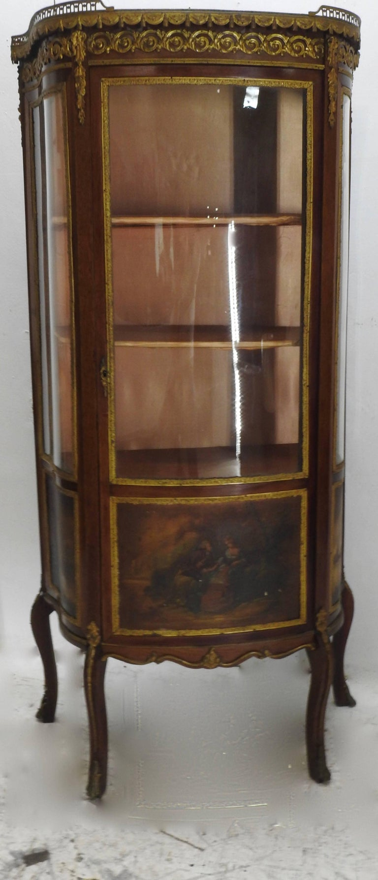 We are offering a beautifully detailed French Vitrine with outstanding Ormolu features. The top is finished with grey and rust colored marble and is framed with fencing. Gold satin lines the interior. Three pieces of curved glass add to the beauty.