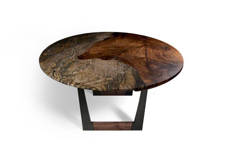 The Granite Pangea table by Taylor Donsker features a single granite slab seamlessly integrated into the top of a single slab of highly figured Bastogne walnut that is resting upon two U-shaped blackened steel and Bastogne walnut bases. The result