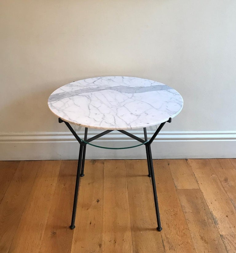 A painted black iron two-tier side table. With circular Carrara marble top (replaced) and clear glass shelf. Designed by the French, 20th century designer Charles Ramos.