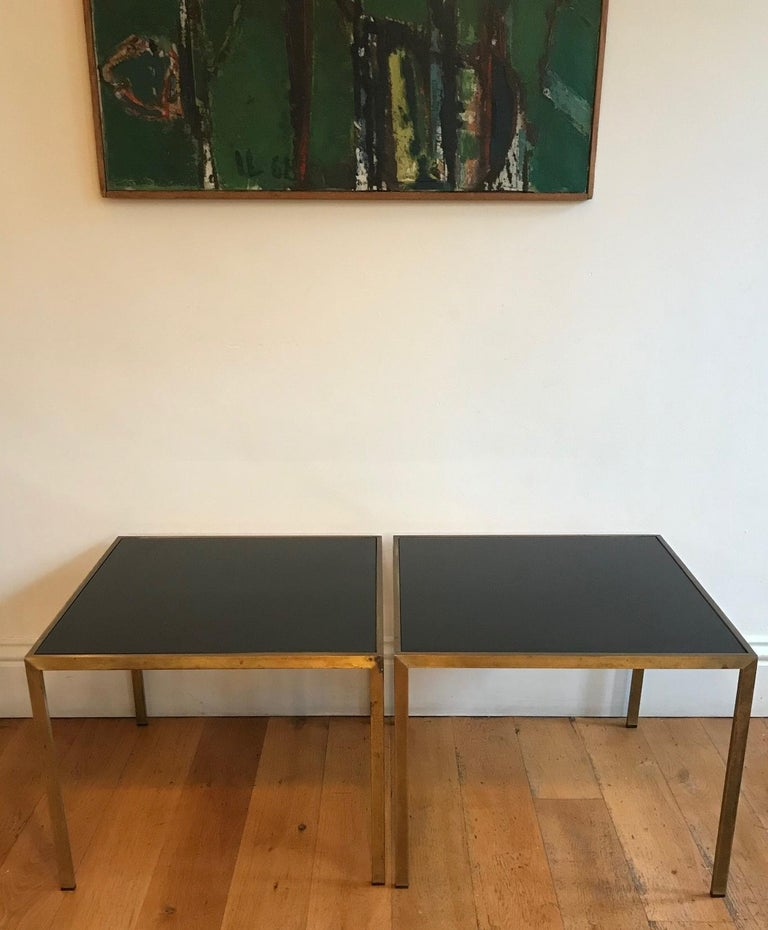 A very elegant pair of gilt metal and black glass side tables. French, circa 1970s. Will complement both a classical and modern interior due to its timeless classic design. The tops have been replaced as the originals were damaged.