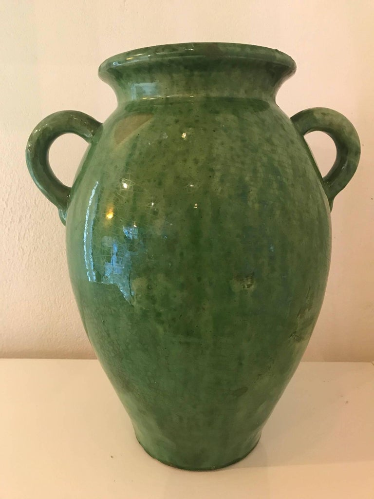 A beautiful tall green glazed ceramic vase or jug made by the French Biot Company.