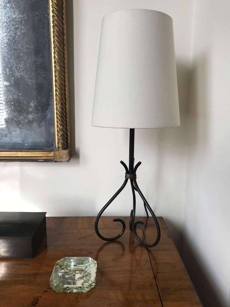 A black iron table lamp with twisted gilt metal rope detail in the manner of Jacques Adnet, French, circa 1950s.