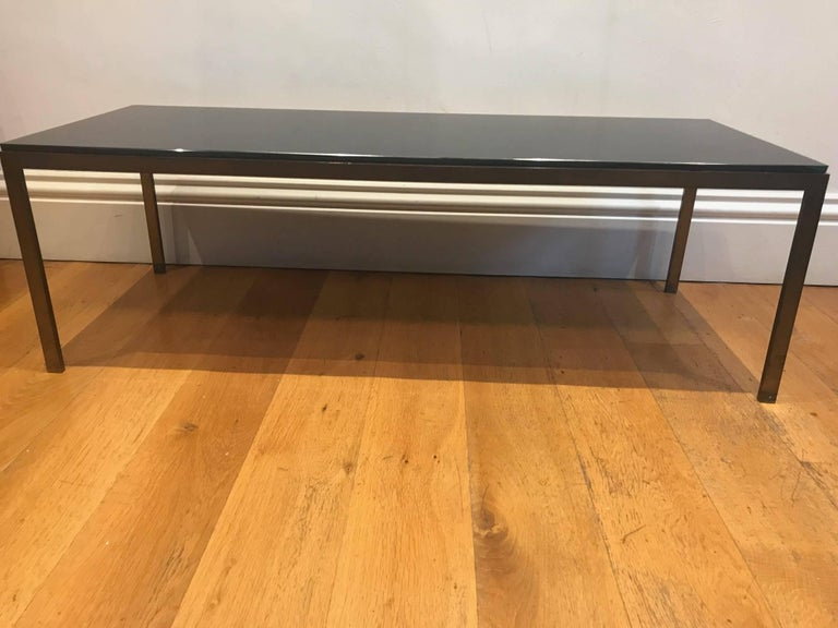 A very sleek and elegant solid bronzed metal and black glass coffee table, French, circa 1950s.