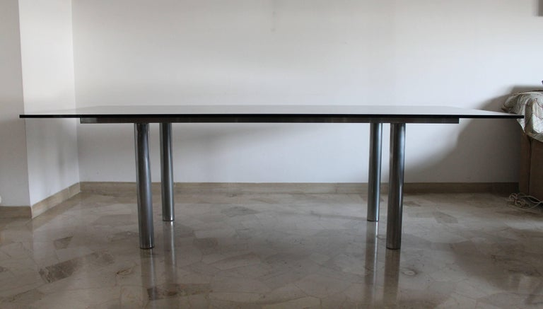 Andre dining table XL size designed by Tobia Scarpa for Gavina, dated 1970.  Smoked glass top on chrome structure.  Very small defect on glass top.