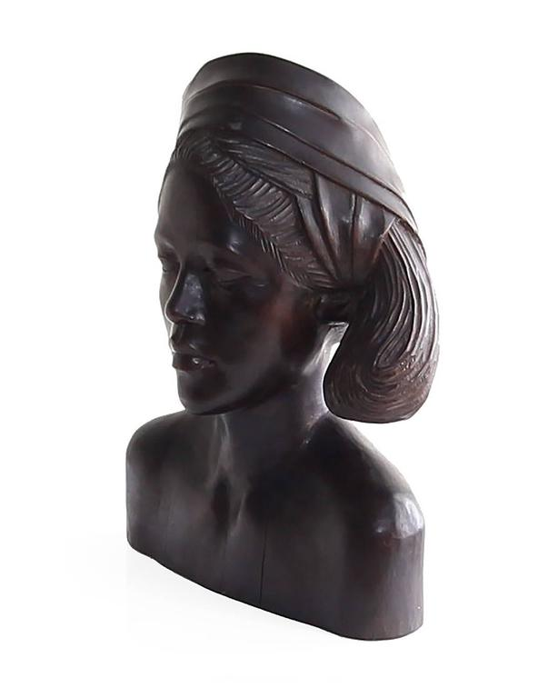 Beautiful carved mahogany wood bust of an Balinese woman wearing a headscarf. This piece is a fine example of traditional wood carving techniques. Powerful specimen with a lot of visual interest and presence. Circa 1950's.