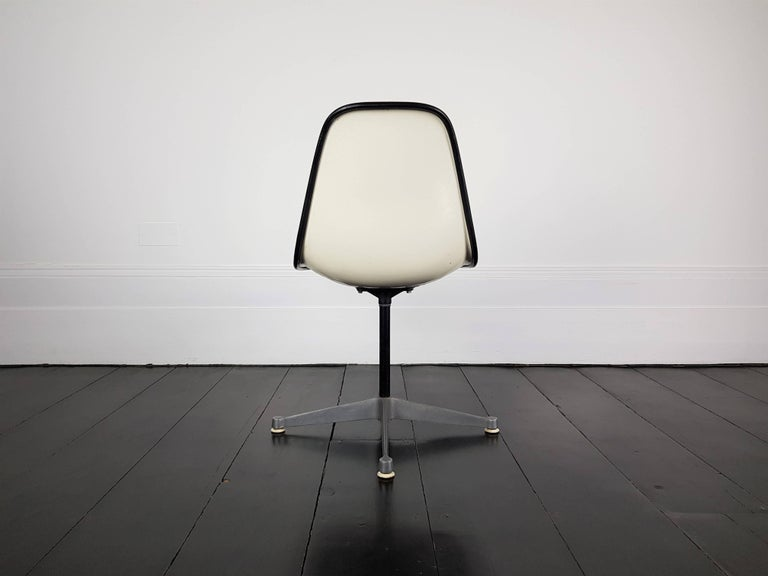 An original vintage vinyl upholstered Charles and Ray Eames fibreglass shell chair on contractor swivel base. Manufactured by Herman Miller, stamped 1975.