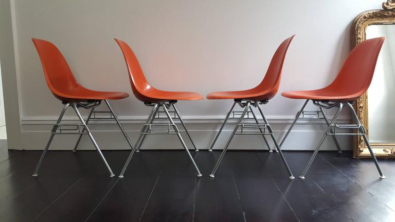 Classic icons, a set of four vibrant orange fiberglass Charles and Ray Eames designed Herman Miller DSS chairs on matt steel stacking bases.