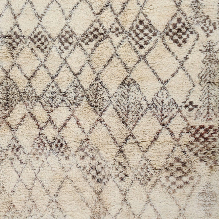 Welcome to the metaphysical world of Beni Ouarain weavers. This authentic Berber carpet with a biomorphic pattern is hand-knotted with a soft blend of subtle browns on a field of natural golden-white wool. The Beni Ouarain tribe produces some of the