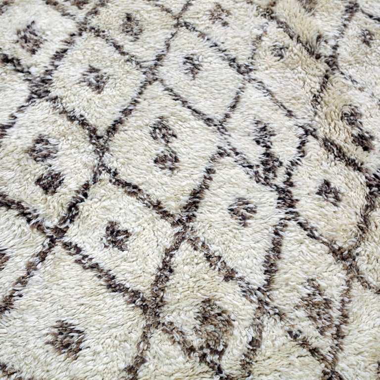 This authentic ivory white Beni Ouarain carpet is hand-knotted with a soft blend of subtle browns and natural wool colors. The Beni Ouarain tribe produces some of the finest quality rugs in all of Morocco. These rugs show an archaic symbolism that
