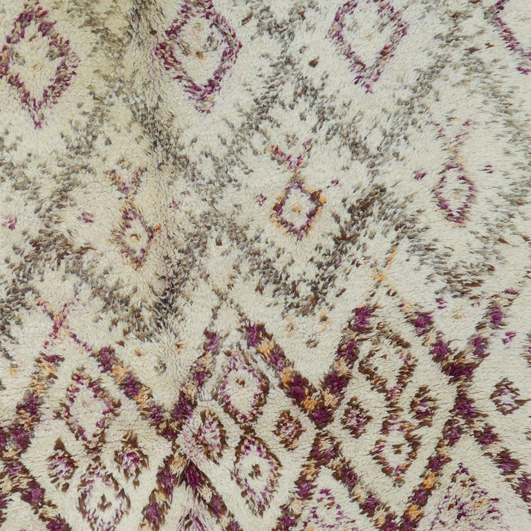 This authentic Beni Ouarain carpet deviates from the norm and is emblazoned with colorful accents that give it a singular beauty. The Beni Ouarain tribe produces some of the finest quality rugs in all of Morocco. These rugs show an archaic symbolism