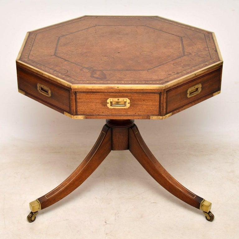 Antique mahogany Campaign style drum table with an octagonal top inset with the original tooled leather which has aged really well and shows plenty of character. The top has a brass top rim, inset brass military handles on the drawers and more brass