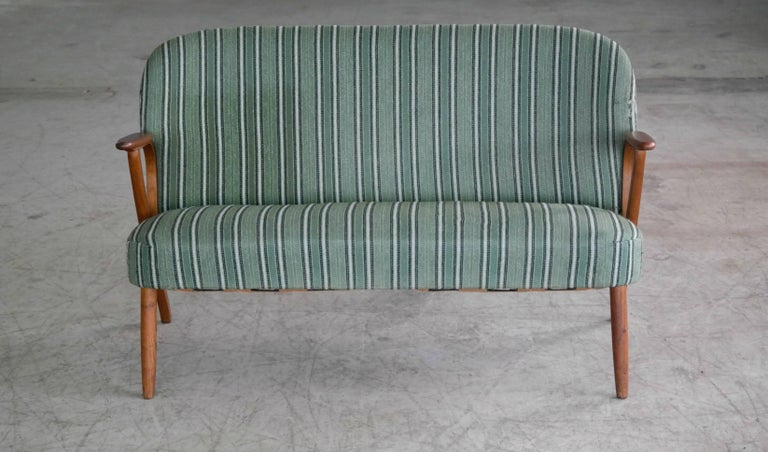 Beautiful and elegant small 1950s Danish sofa with legs and armrests in teak. The high quality woodwork and design is very much in the style of Arne Hovmand Olsen and N.A. Jorgensen (Bramin Mobler) but it is unmarked and a rare piece and we cannot