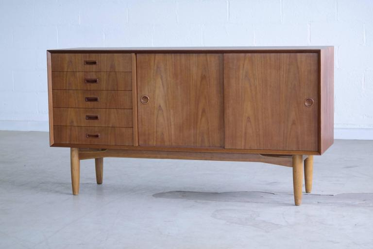 Mid century classic Omann Jun design and quality. This Low teak credenza with carved pulls on a base of solid oak provides lots of storage space and packs a punch for its size.