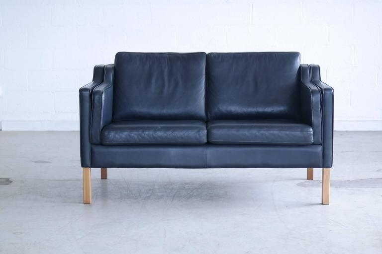 Very elegant and comfortable Classic Børge Mogensen style sofa model 2212 in Dark Sapphire navy blue leather by Stouby Polsterfabrik of Denmark. High quality leather over a beech wood frame and legs. Cushions are top filled with down. Nice worn in