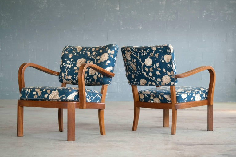 Very versatile and stylish pair of open armchairs made in solid oak. The chairs are attributed to Fritz Hansen but unmarked. Overall very good condition but the fabric shows a bit of sun fading.