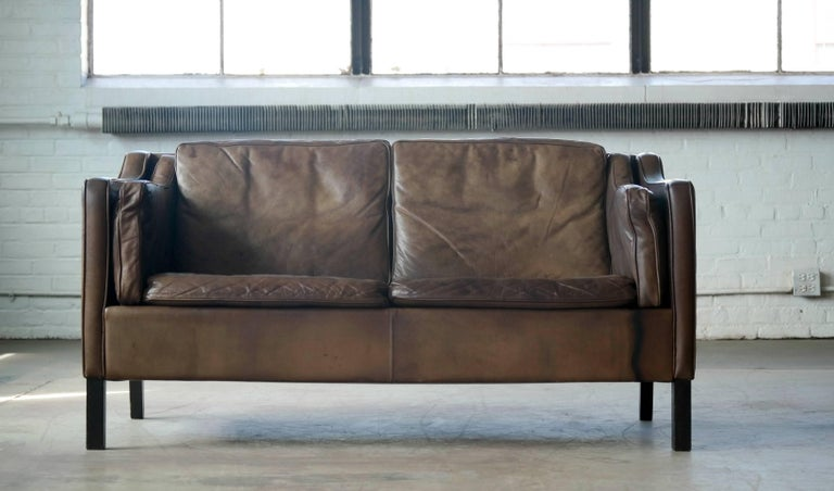 Classic Borge Mogensen style two-seat sofa or loveseat in the style of Borge Mogensen produced by Mogens Hansen. Has achieved that admirable patina that only the combination of aniline buffalo leather and time can produce. Fantastic patina and