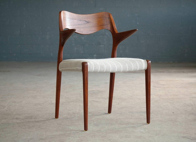 This wonderful Danish modern teak armchair by NO Moller was designed in 1955 for J.L. Møllers Møbelfabrik. Beautiful versatile chair that works equally well as a work chair with your desk or at the helm of the dining table. Beautiful hand-carved