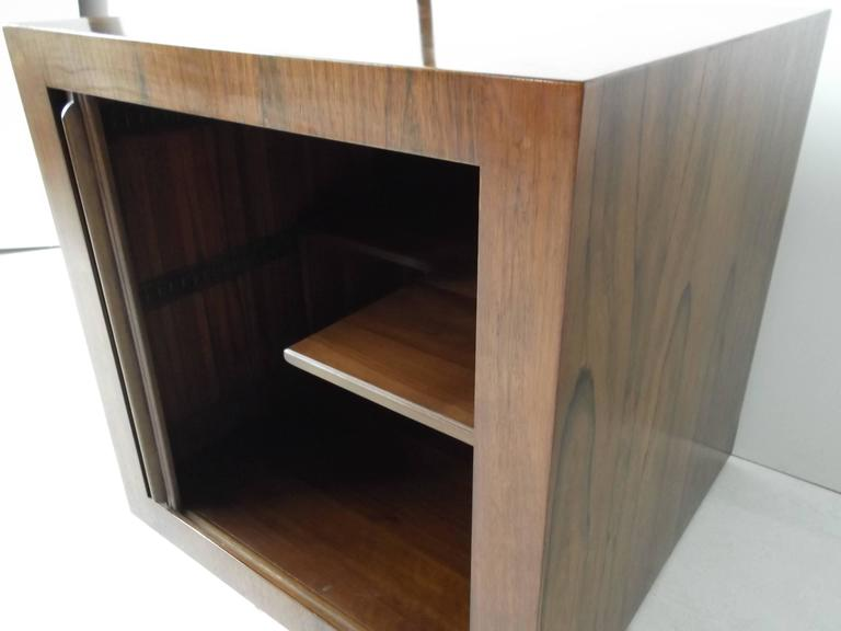 Gorgeous figural rosewood, finished to all sides, rolling barcart cube table. Features tambour door, internal cut-out shelf for bottle storage.