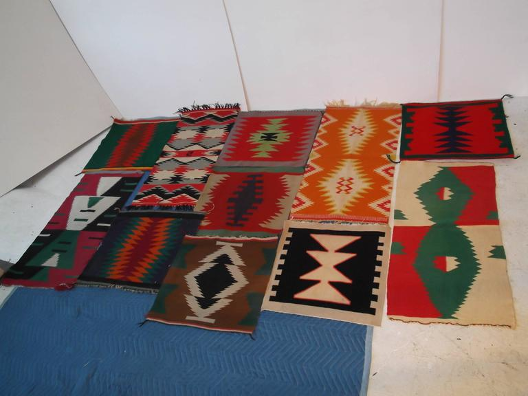 This is an amazing collection of 11 Germantown wool, Indian rug samplers. The first pictures are to fronts, and the last picture is the backside to all. There are four elongated, and 7 more squarish shaped rugs. They are in a variety of colors and