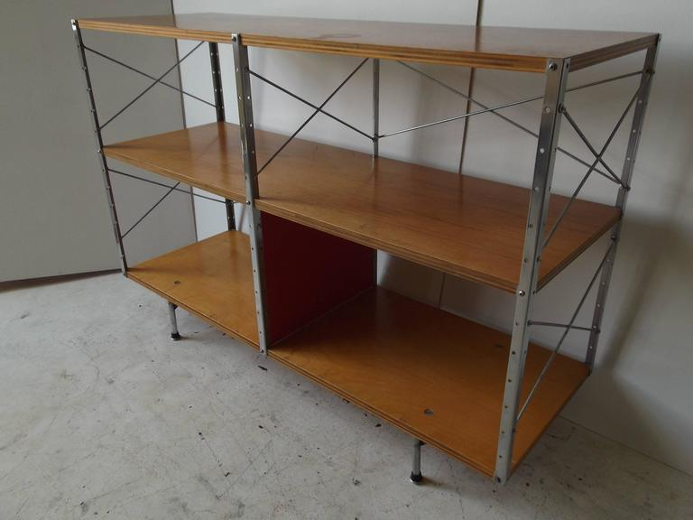 This is a great example of an original Charles Eames Storage Unit for Herman Miller. It has 2nd series feet. There is one bright red panel to the bottom center. The top and middle shelves are beautiful veneer walnut on plywood, with the bottom in