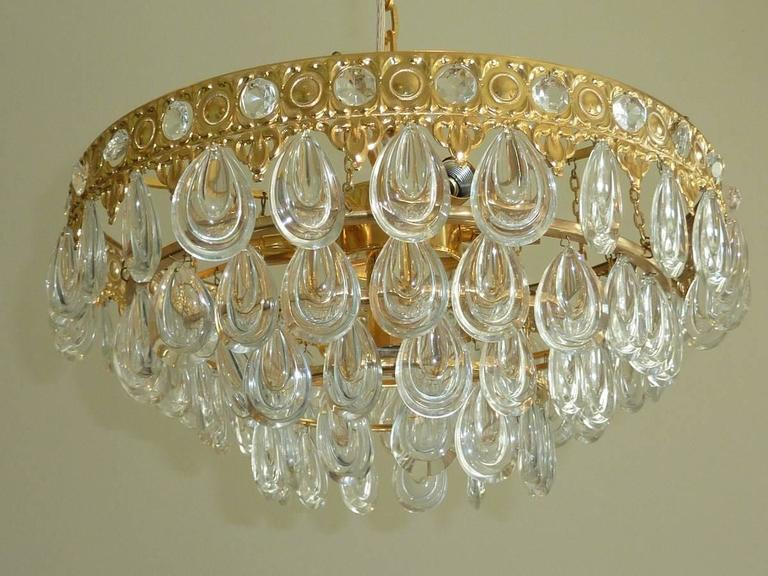 Beautiful chandelier made by Palwa in Germany, 1970s. A gilt brass frame with four rows of teardrop-shaped glass in very nice original condition. The Flush Mount requires seven European E14 candelabra bulb, each bulb up to 40 watts.It holds 7 bulbs.