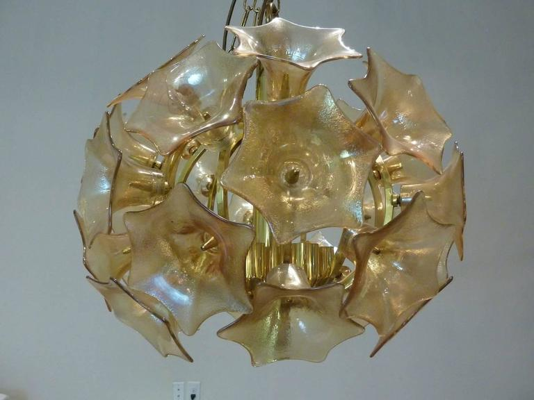 Vintage 1960s amber glass light fixture. Constructed of multi flowers brightened by E14 candelabra European bulbs. Beautiful addition to any upscale surrounding.