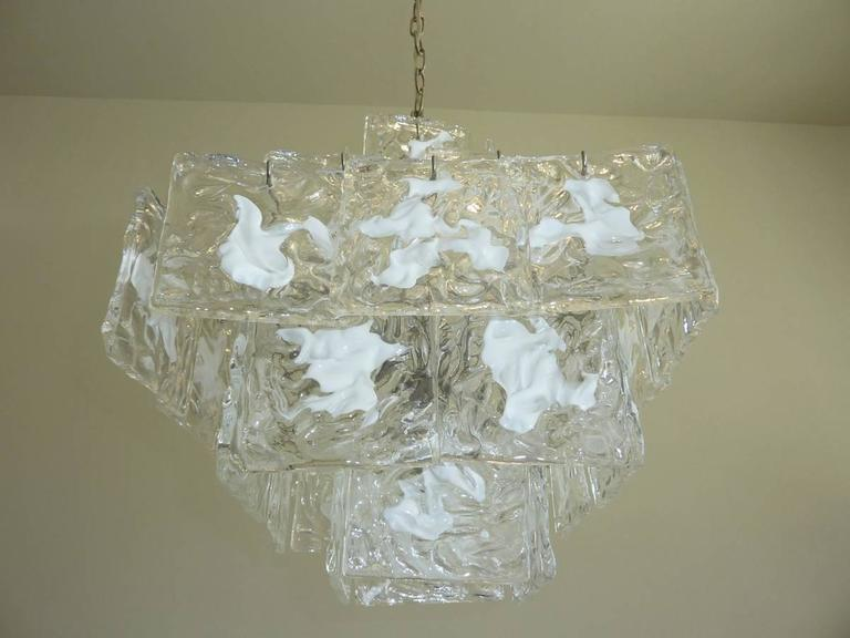 Five-tiered Murano glass chandelier with clear and white textured glass square slabs arranged in a cube shape. Glass squares are suspended from silver tone armature. The 1960s era chandelier has four upwards facing candelabra sockets for European