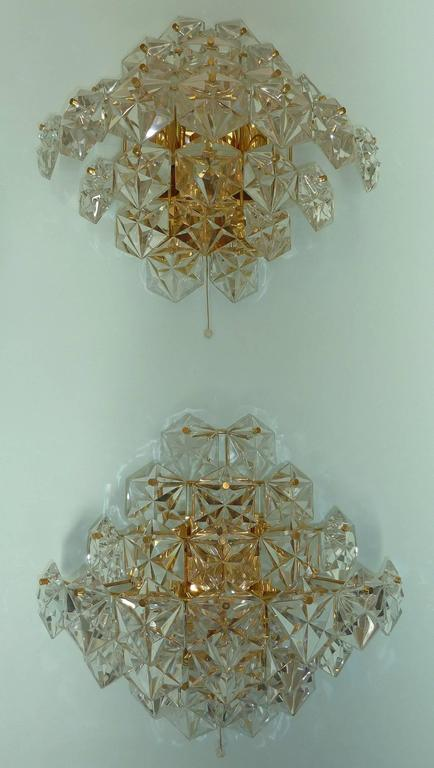 Impressive pair of Kinkeldey sconces with 27 faceted hexagonal crystals on polished brass hardware. The 1960s sconces are semicircular in profile and have an overall diamond shape. There are three sockets; two facing downward, one facing upward.
