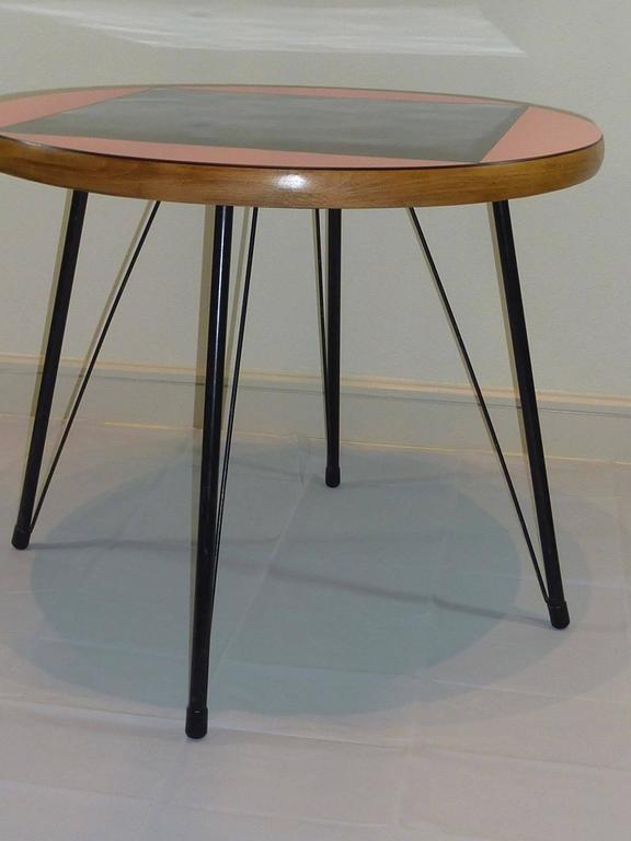 Petite Mid-Century dining table from the Rock a Billy Era. Made of small metal feet and a plywood tabletop. Colored in pink with a black inlay.