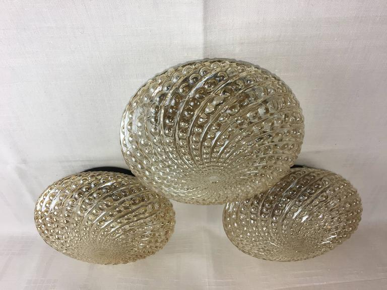 Three round circa 1960s German bubble glass sconces or flush mount with interior lights. Each fixture requires one European e14 candelabra bulb, each bulb up to 40 watts.