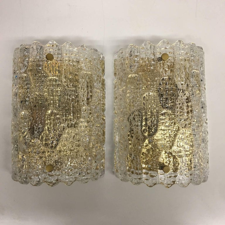 Beautiful sought after Lot of wall sconces by Carl Fagerlund for Orrefors. Pressed textured glass with brass accents mounted on brass wall plates. Each Fixture requires two European E14 candelabra bulbs, each up to 60 watts.