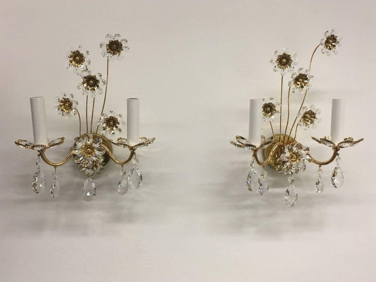 Pair of vintage gold-plated sconces with faceted crystal flowers made by the German company Palwa. Each fixture has two European style E14 sockets. It requires two European E14 candelabra bulbs.