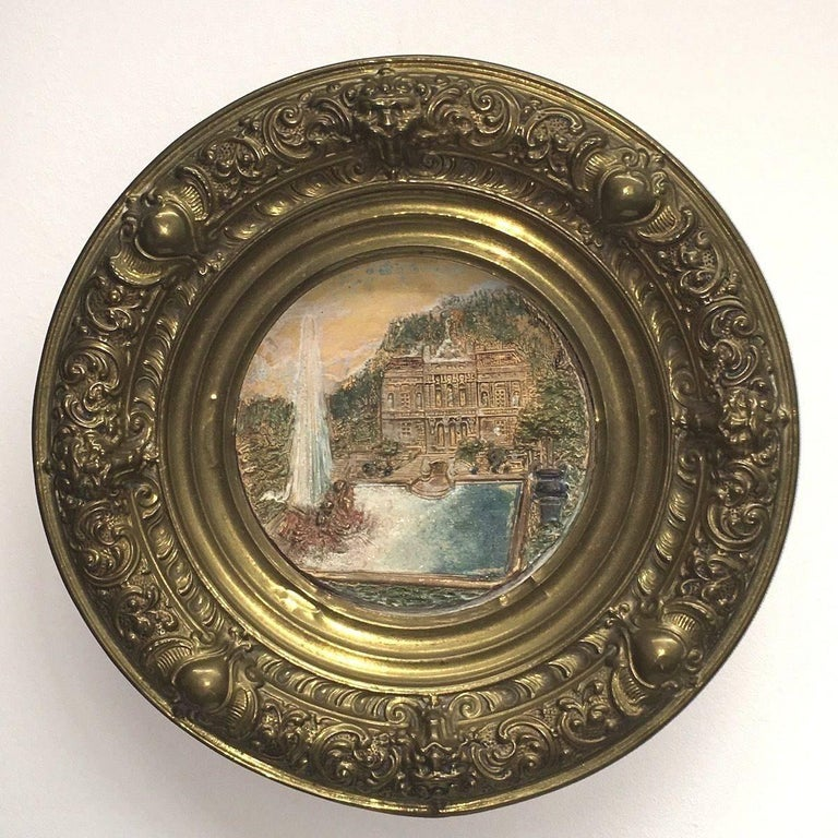 A large German faience plate framed by brass, circa 1880. The faience plate represent castle Linderhof in a landscape. The brass is entirely decorated with flowers, hearts and lions. Very elegant reflection of the era  and a lovely display of King