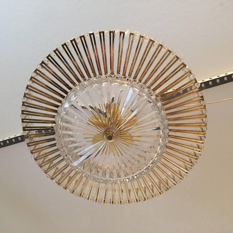 A grand 1970s Austrian crystal glass Lucite and gilt brass chandelier attributed to the style of Lobmeyr. The lamp is wired to be staged in a three or six light configuration. It requires six European E14 Candelabra bulbs to produce it's wonderful