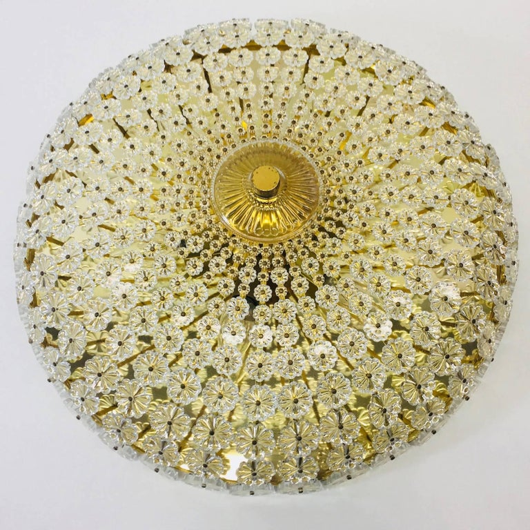 Large flower shaped flush mount designed by Emil Stejnar in the 1960s in Austria. It features a brass frame with hundreds of lovely crystal glass pieces designed to portray the image of a spectacular flower surrounding the frame. This flush mount
