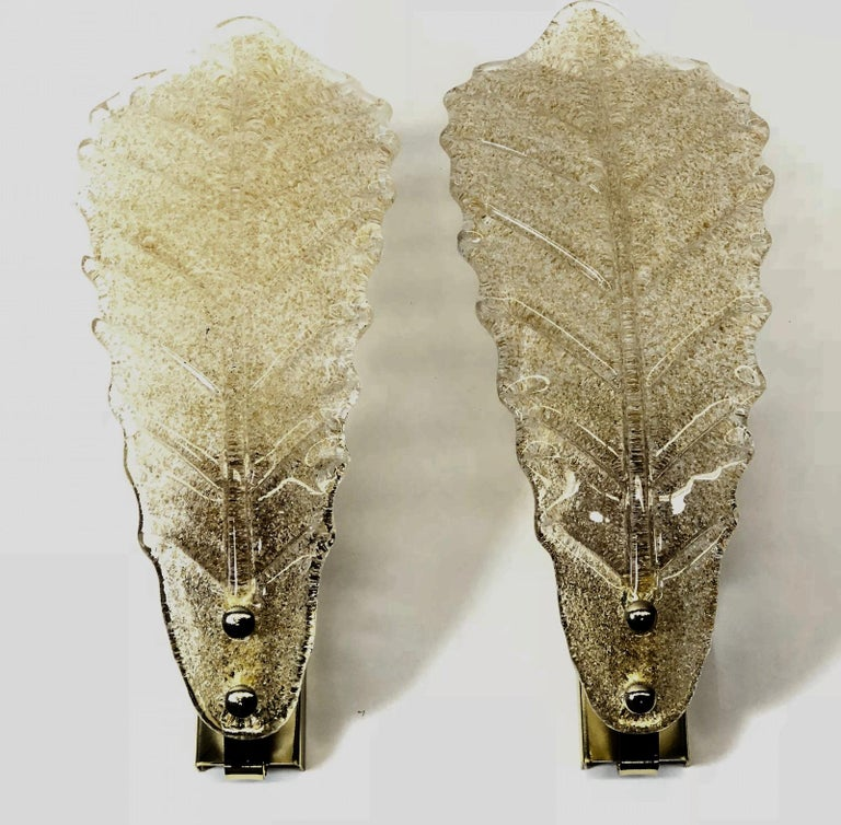 A stunning pair of Murano glass leaf wall sconces. Each consisting of a stylish single leaf design. A single brass wall plate with a solo socket and mount make for a beautiful wall light. Easy to mount and fantastic to look at. each fixture requires